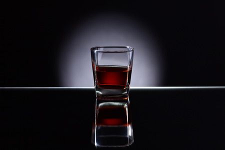 alcoholic drink: Glass with  alcoholic drink on a reflective background