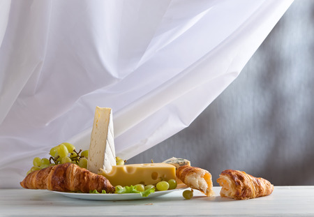 bri: cheese with grapes and croissants on white table