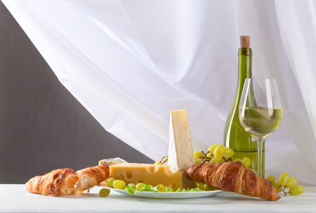 bri: cheese with grapes ,croissants and wine on white table