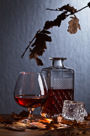 Snifter of brandy and dried oak leaves on wooden table