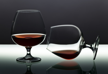 snifter: Two snifters of brandy on the reflective background Stock Photo