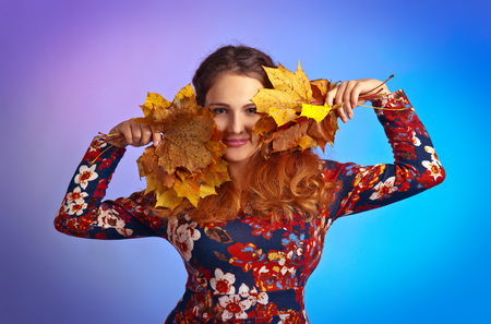 beautiful autumn woman in studio with yellow maple leaves photo