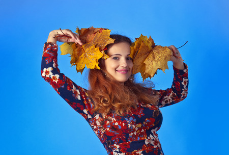 beautiful autumn woman in studio with yellow maple leaves on blue background photo