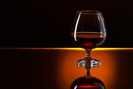 brandy: Snifter with brandy on a reflective background