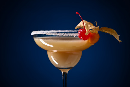 sweet vermouth: Cocktail with physalis and cherry on a blue background