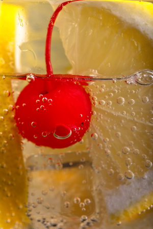 food and drink: cold carbonated drink with lemon and sweet cherry