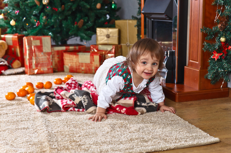 Little girl on the carpet in the room with Christmas decorations Stock Photo