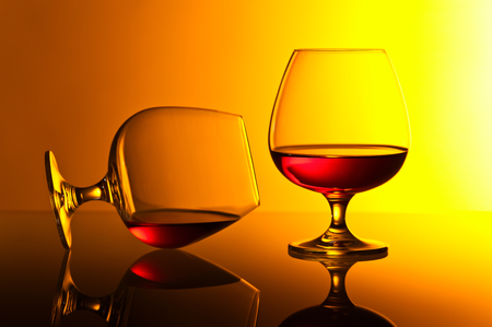 snifter: Two snifters of brandy on yellow background Stock Photo