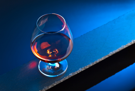 snifter: Snifter with brandy on a blue background