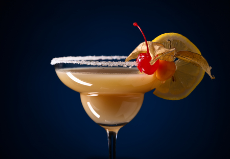 sweet vermouth: Sweet cocktail with physalis , cherry and lemon  on a dark blue background