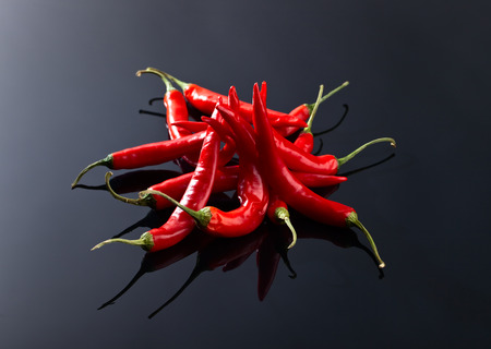 beam of red chilli pepper on a black background Stock Photo