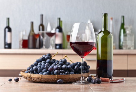 Glass of red wine and grape on a kitchen table Stock Photo