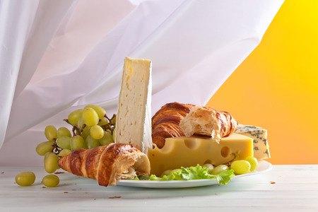 bri: cheese with grapes and croissants on white wooden table