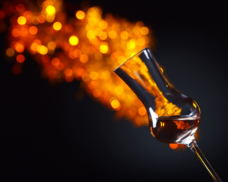 alcoholic drink: Glass of alcoholic drink on a dark background