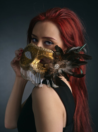 redheaded: Beautiful redheaded woman in  black dress with carnival mask