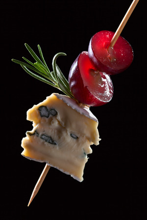 Blue cheese with grape and rosemary on a black background Stock Photo