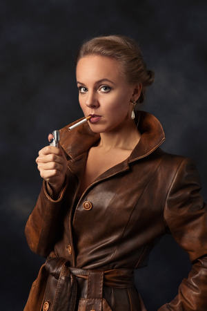leather coat: Portrait of young beautiful woman in brown leather coat with lighter and cigarette Stock Photo