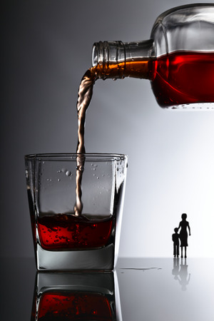 alcoholismo: bottle and glass of whiskey , alcoholism in the family Foto de archivo