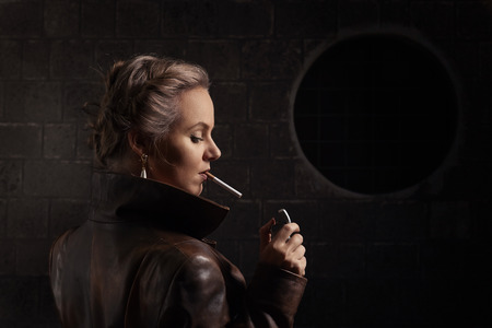 leather coat: beautiful woman in brown leather coat with lighter and cigarette Stock Photo