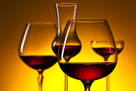 snifter: Glasses of brandy on a yellow background Stock Photo