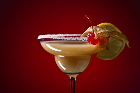 sweet vermouth: Sweet cocktail with physalis , cherry and lemon on red background Stock Photo