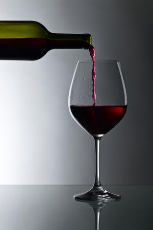 ボトルと暗い背景に赤ワインのガラス 写真素材