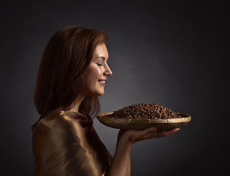 Young pretty woman with roasted coffee beans Stock Photo