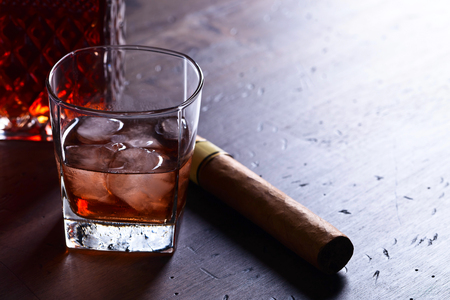 Glass of whiskey with natural ice on a old wooden table Stock Photo