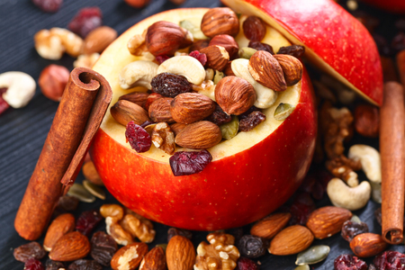 Red juicy apple with assorted nuts , raisins and cinnamon sticks