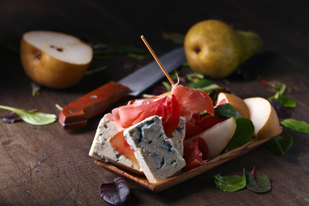 blue cheese with prosciutto and pear on a old wooden table