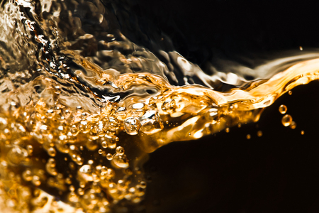 splashing of alcoholic drink on a black background, free space for your text Standard-Bild