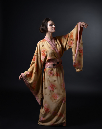 young dancing woman in traditional Japanese kimono on black background Stock Photo