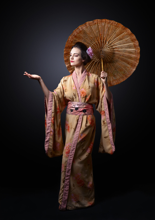 young beautiful woman in traditional Japanese kimono with umbrella Stok Fotoğraf - 72767899