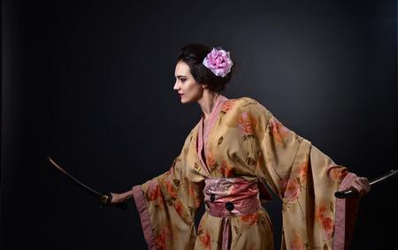 young beautiful woman in traditional Japanese kimono with katana