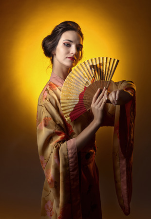 young beautiful woman in traditional japanese kimono with open fan Stock Photo