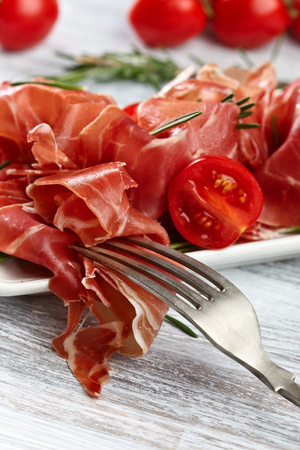 Prosciutto with  rosemary and tomato on a old wooden table