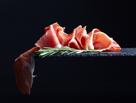 prosciutto with rosemary on a black reflective background Фото со стока