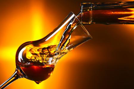 Gießen Alkohol in ein Weinglas auf dunklem Hintergrund