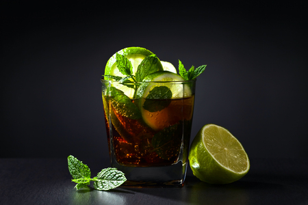 Cola with lime , ice  and peppermint on black table