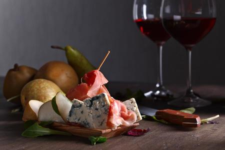 古い木製のテーブル上の梨と生ハムのチーズ 写真素材