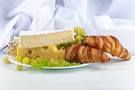bri: breakfast with cheese and croissant on white table