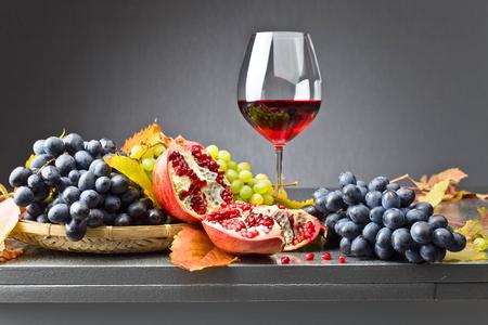 ブルー イザベラ ブドウの束、緑色のブドウは秋の紅葉と台所のテーブルに熟したザクロ束します。赤ワインのガラス。