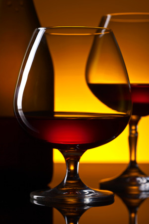 Two glasses of brandy and bottle on the reflective background