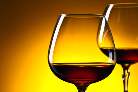 snifter: Two glasses of brandy on yellow background . Selective focus . Free space for your text. Stock Photo