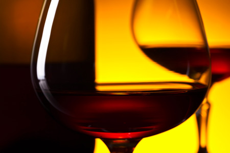 Two glasses of brandy and bottle on yellow background . Selective focus .