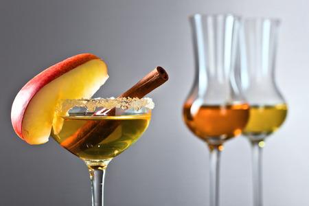 Bicchiere di bevanda alcolica dolce con mela e cannella guarnite con zucchero.