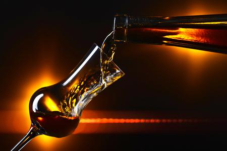 Alkoholisches Getränk in ein Weinglas auf dunklem Hintergrund gießen Standard-Bild