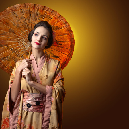 young beautiful woman in traditional japanese kimono with umbrella .  Copyspace. Perfect hair with pink chrysanthemum. Beauty woman with perfect makeup. Beautiful professional  make-up .Hairdressing. Stock Photo