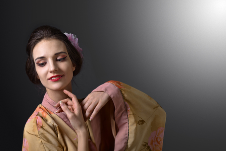 Young beautiful woman in traditional Japanese kimono .Perfect hair with pink chrysanthemum. Beauty brunette woman with perfect makeup. Beautiful professional  make-up .Hairdressing.