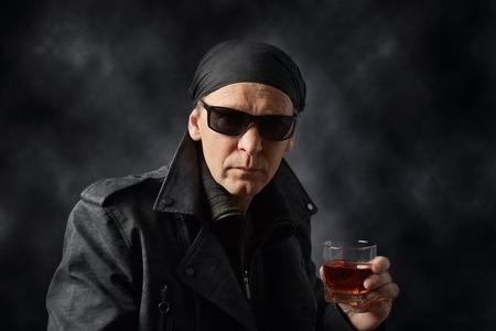 innovative design 1a9d3 26cf1 Ritratto di un uomo di mezza età in una giacca di pelle nera, occhiali da  sole e bandana nera. Rastrello con un bicchiere di whisky su sfondo nero.